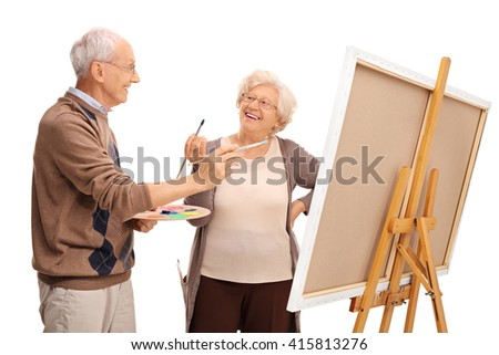 Mature couple painting on a canvas and having fun isolated on white background - stock photo