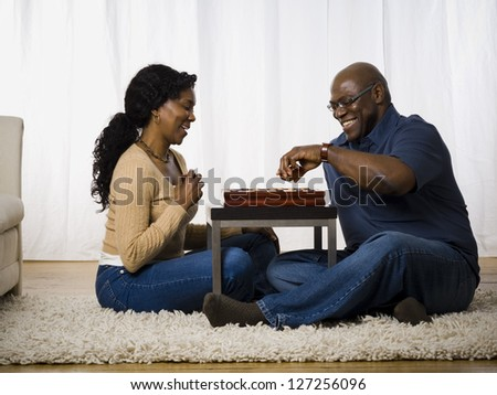 Mature couple playing a board game - stock photo