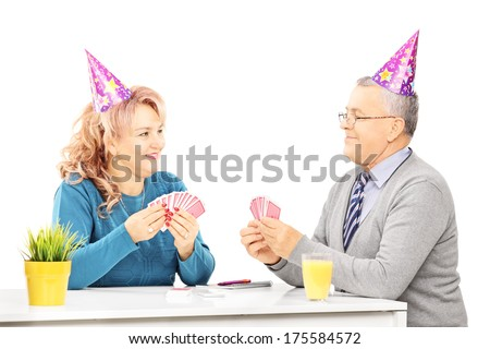 Mature couple playing cards on table at a party, isolated on white background - stock photo