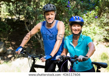 Mature couple posing with their bike on the wood - stock photo