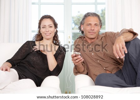 Mature couple sharing headphones while listening to music at home. - stock photo