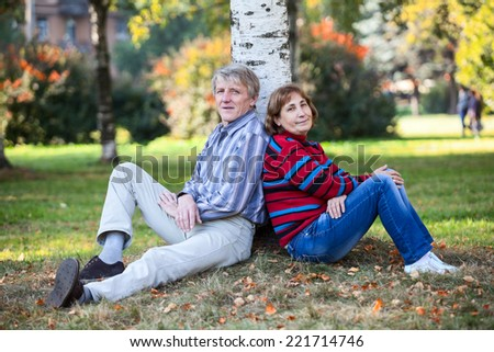 Mature couple sitting back-to-back together behind the tree in autumn park - stock photo