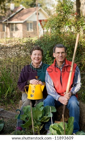 Mature couple sitting on bale of hay in their city garden with collard plants in the foreground. - stock photo