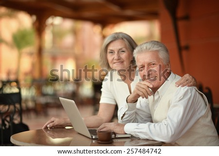 Mature couple sitting with laptop in hotel - stock photo