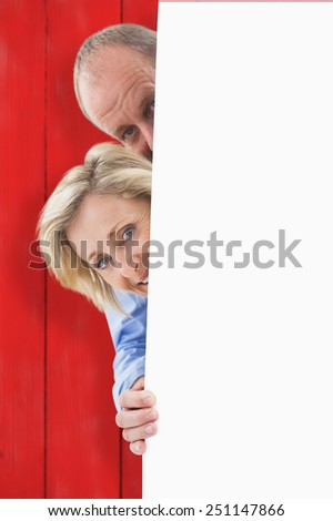 Mature couple smiling behind wall against red wooden planks - stock photo