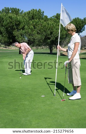 Mature couple standing on putting green, man playing shot, woman holding golf flag, watching - stock photo