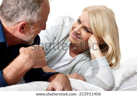 Mature couple talking together on their bed in bedroom  - stock photo