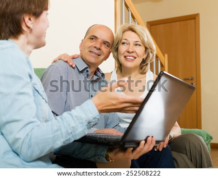 Mature couple talking with employee with laptop at home