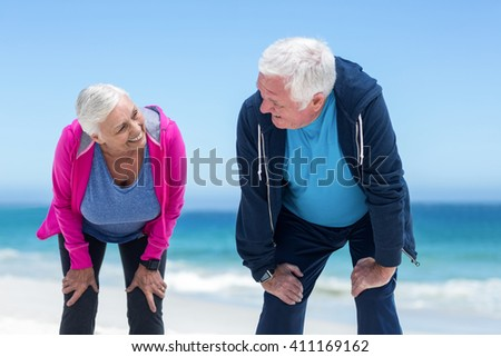 Mature couple tired after running on the beach - stock photo