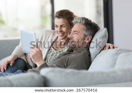 Mature couple using digital tablet relaxing in sofa - stock photo