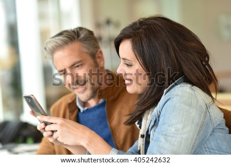 Mature couple using smartphone in coffee shop