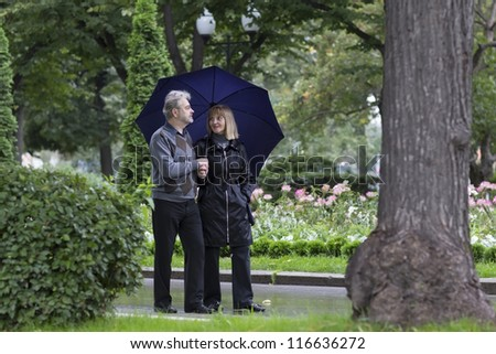 Mature couple walking in a park on a rainy day