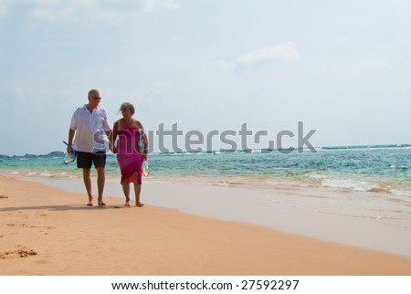 Mature couple walking on tropical beach holding hands, the ocean is turquoise blue. - stock photo