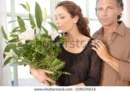 Mature couple with bunch of flowers at home.