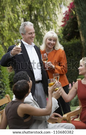 Mature couple with friends toasting wine together - stock photo