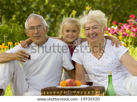 Mature couple with grandchild picnicked on the grass - stock photo