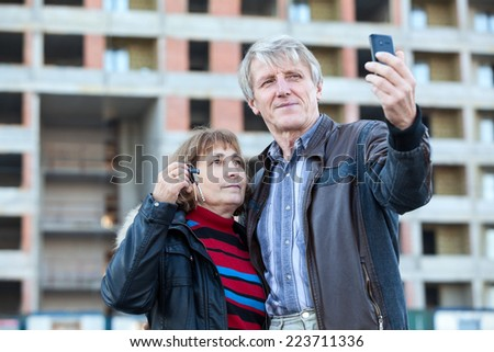 Mature couple with house keys in hand making cellphone selfie - stock photo