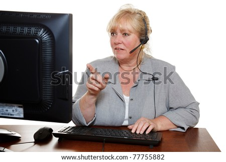 Mature customer service representative with headset points at the monitor