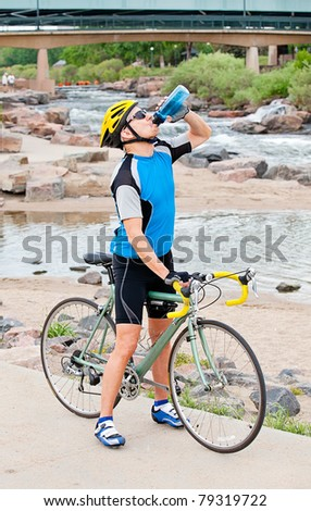 Mature cyclist takes a break in a city park by the river - stock photo