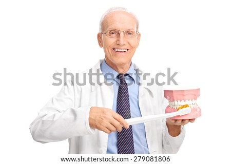 Mature dentist holding a large toothbrush and a denture and looking at the camera isolated on white background - stock photo