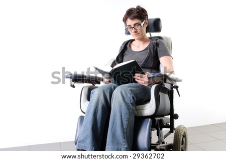 Mature disabled woman in a wheelchair, reading - stock photo