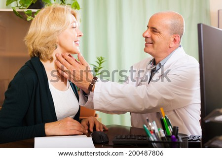 Mature doctor checking thyroid of smiling woman  in clinic - stock photo