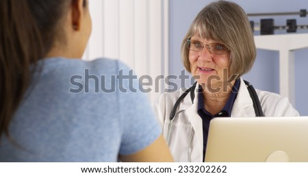 Mature doctor consulting Hispanic woman patient - stock photo
