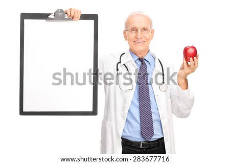 Mature doctor holding a red apple and a clipboard with a blank white paper on it isolated on white background - stock photo