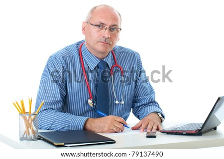 mature doctor in blue shirt sits at his desk, makes some notes, isolated on white