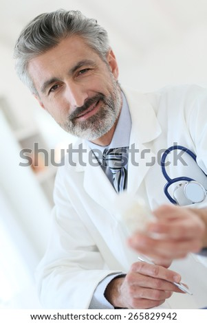 Mature doctor in hospital giving pills to patient