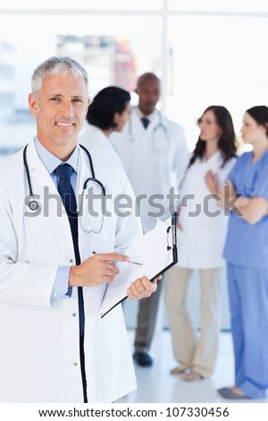 Mature doctor smiling while pointing to a sentence on his clipboard - stock photo