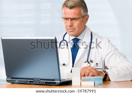 Mature doctor working on laptop and medication's cases to make prescriptions in his clinic office - stock photo