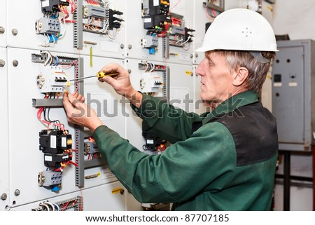 Mature electrician maintaining high voltage control panel in hard hat with screwdriver