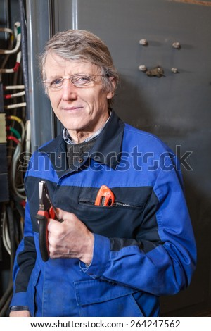 Mature electrician with pliers in his hands standing near high voltage box - stock photo