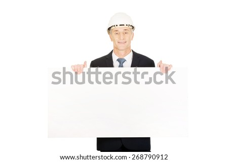 Mature engineer with hard hat holding empty banner.