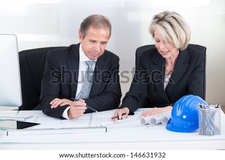 Mature Engineers Looking At Plans Sitting At A Table - stock photo