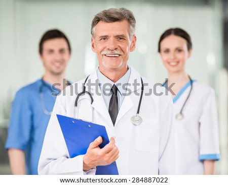 Mature experienced doctor with young colleagues at doctor's office. - stock photo
