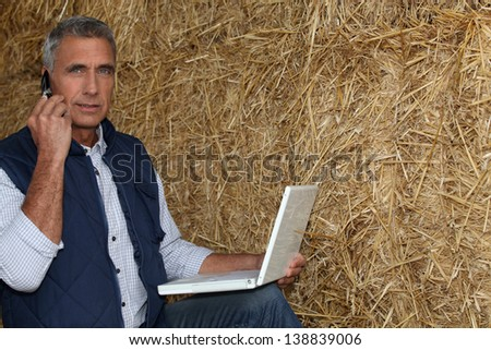 mature farmer on the phone with laptop against hay background - stock photo