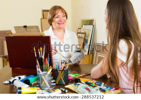 Mature female artist painting portrait of young girl at art studio with pencil and paints  - stock photo