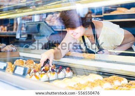 mature female baker offering fresh pastry at the counter in sweet-shop