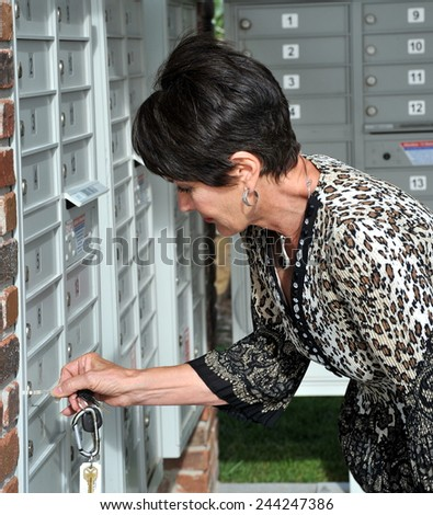 Mature female beauty at her mailbox outside. - stock photo
