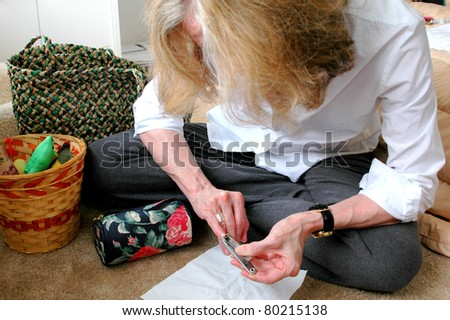 Mature female beauty doing her nails at home to relax after working all day. - stock photo