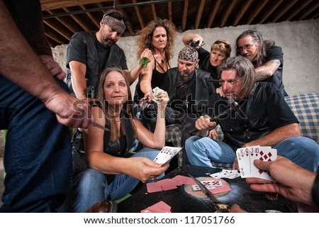 Mature female biker gang member shows cards to aggressive players
