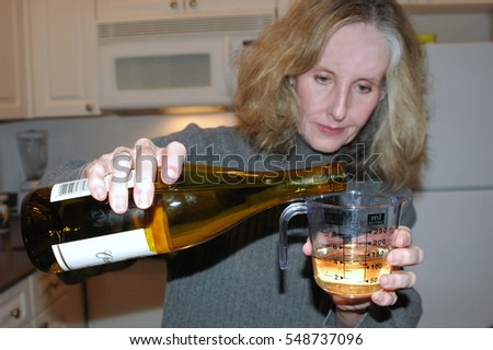 Mature female blond beauty cooking dinner with wine.
