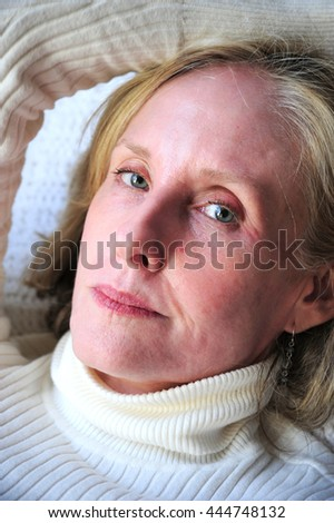 Mature female blond beauty expressions indoors.