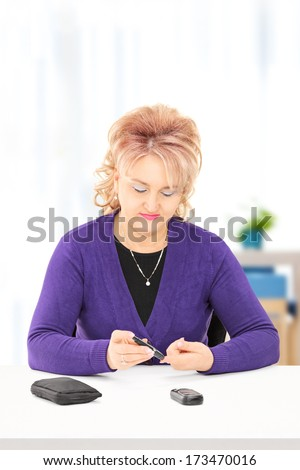 Mature female checking her blood sugar level, at home - stock photo