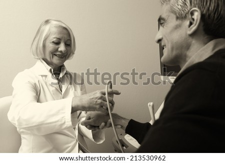 Mature female doctor scanning man in 40s. Wrist and arm exam.