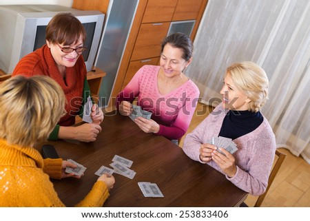 Mature female having fun with pack of cards indoor - stock photo