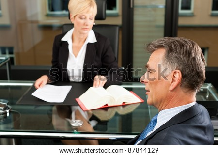 Mature female lawyer or notary with client in her office for counseling - stock photo