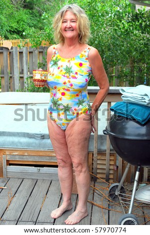Mature female on her patio deck standing next to her hot tub. - stock photo